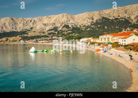 Beautiful view of the the seaside resort of Baska on the Croatian island of Krk in the Adriatic sea with hotels, tourists, beach goers and vacationers - Stock Photo