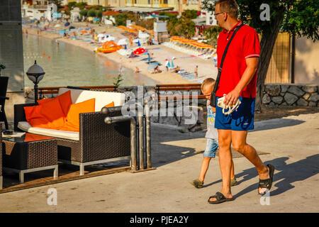 People strolling near Baska Beach resort on the Krk Island in Croatia - Stock Photo