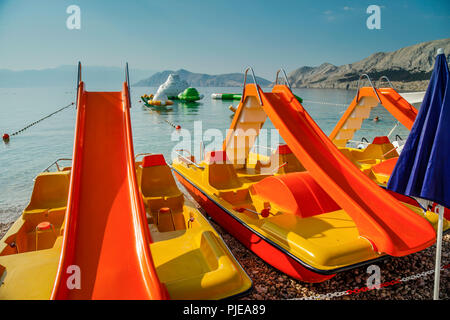Beach slides and water sport toys at Baska resort on the Croatian island of Krk in the Adriatic - Stock Photo
