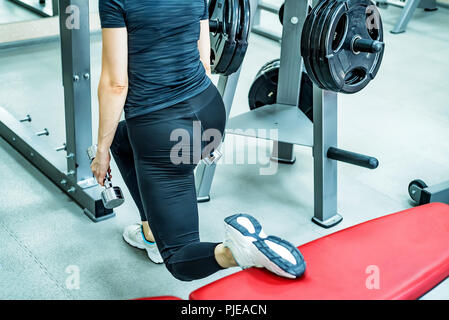 Young woman does leg lunge exercises in gym - Stock Photo