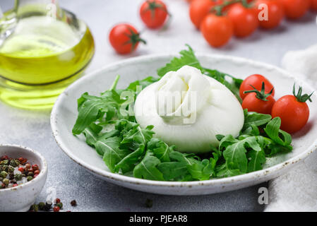Delicious Italian fresh burrata cheese with arugula salad, cherry tomatoes and olive oil in a white plate. Gourmet snack. Selective focus - Stock Photo