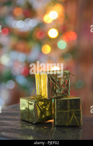 Set of golden gift boxes with defocused Christmas decoration in the background get a beautiful blur to complete a design, for postcards or calendars - Stock Photo