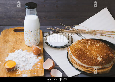 fresh, hot pancakes in a frying pan, eggs, milk, flour on a wooden table - Stock Photo