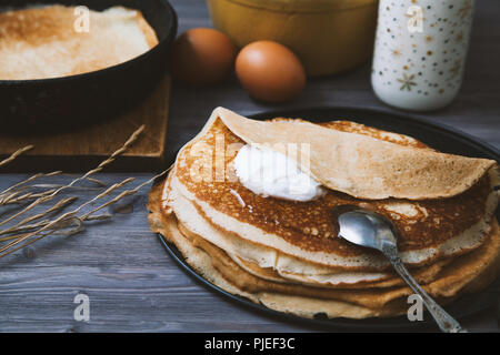 Pancakes in a skillet and ingredients for them on a wooden table. - Stock Photo