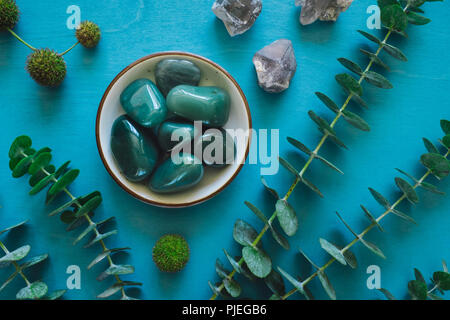 Green Aventurine with Quartz and Eucalyptus on Turquoise Table - Stock Photo