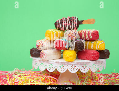 Close up on many colorful candy coated popsicle cake pops stacked on a white pedestal with bright paper party streamers below, bright green background - Stock Photo