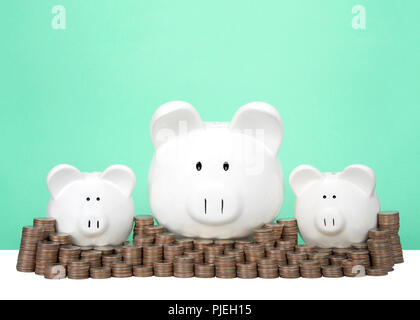 Three piggy banks in a row one large two small behind a wall of coins stacked in piles. Wall of savings. Dollar signs in their eyes. Light green backg - Stock Photo