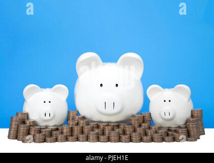 Three piggy banks in a row one large two small behind a wall of coins stacked in piles. Wall of savings. Dollar signs in their eyes. Blue background w - Stock Photo