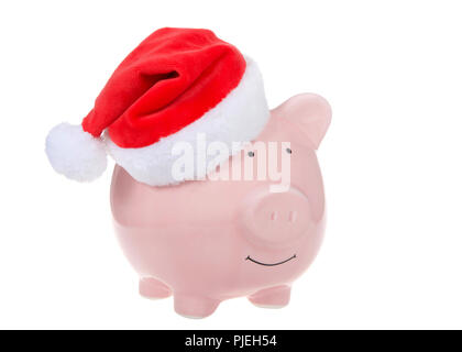 Pink piggy bank wearing a Santa hat smiling facing viewers right isolated on white. - Stock Photo