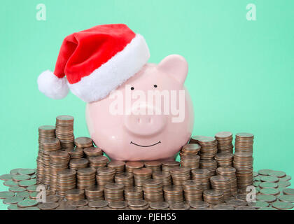 Pink piggy bank wearing a Santa hat smiling facing viewer surrounded by stacks of coins, green background. - Stock Photo