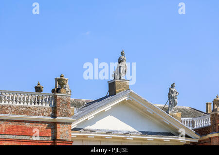 Statues of Roman goddesses above the portico entrance of Avington Park, a Palladian mansion country house in Avington near Winchester, Hampshire, UK - Stock Photo