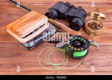 fly fishing rod with a coil and flies lie on old, wooden boards - Stock Photo