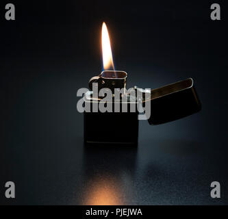 Zippo lighter. Fire starting tool used during camping to start a fire and burn wood. Modern day metal lighter with yellow and orange flame. - Stock Photo