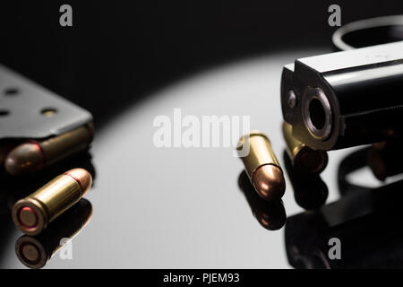 Close up of a barrel of a gun with bullet casings. Live rounds of shell casings from a military hand gun. Weapons of war. Arsenal. - Stock Photo