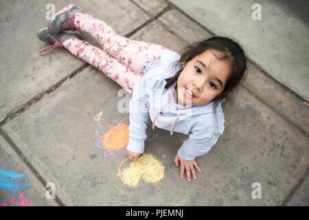 Kids Drawing with Chalk on Sidewalk. - Stock Photo