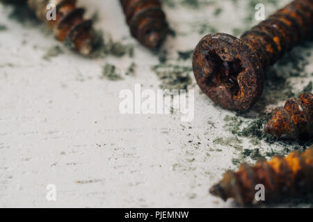 Close up selective focus of rusty screws. old steel bolts on grungy white wood background - Stock Photo