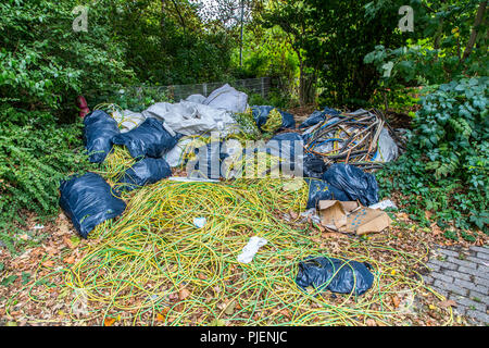 Wild garbage dump on a public parking lot, illegal disposal of construction site waste, cable waste, on a large scale, the garbage was later removed f - Stock Photo