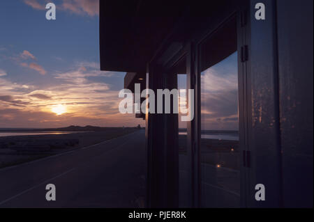 A sunset reflected in the window of a cafe on the beach at Littlehampton, West Sussex, UK. - Stock Photo
