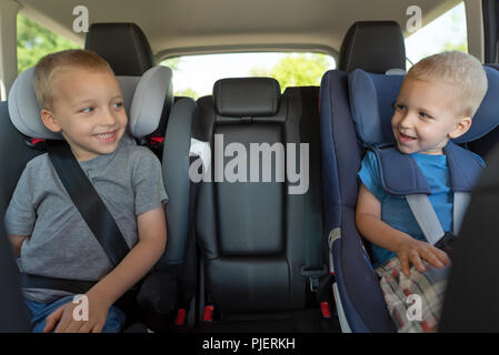 Two boys are driving in car seats. Safety of children while traveling by car - Stock Photo