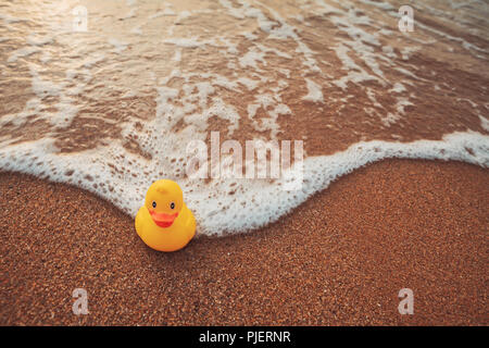 Yellow rubber duck toy floating in sea water. Beautiful sunrise on ...