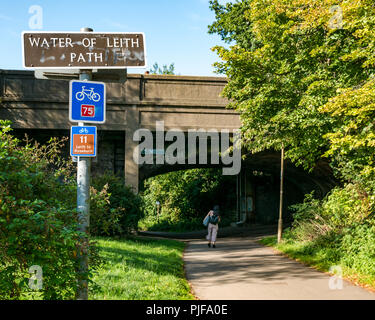 Water of Leith footpath and cycle route sign with woman walking under bridge on sunny day Leith, Edinburgh, Scotland, UK - Stock Photo