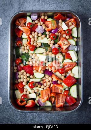 A vegetable medley consisting of chopped raw red peppers, courgettes, red onions and cherry tomatoes with cooked chickpeas, ready to be baked in the o - Stock Photo