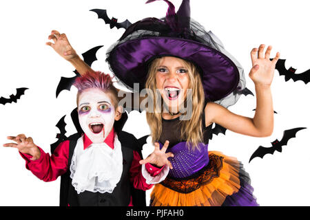 Halloween kids, Happy scary girl and boy dressed up in halloween costumes of witch, sorcerer and vampire, Dracula for pumpkin patch and halloween part - Stock Photo