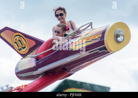 Mother and young daughter enjoying a ride in Dreamland Amusement Park, Margate, Kent, England, uk. - Stock Photo