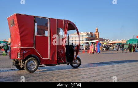 Main market square called Jamaa El Fna in Marrakech, Morocco, red small typical local taxi tuk-tuk, people doing aily shopping.view - Stock Photo