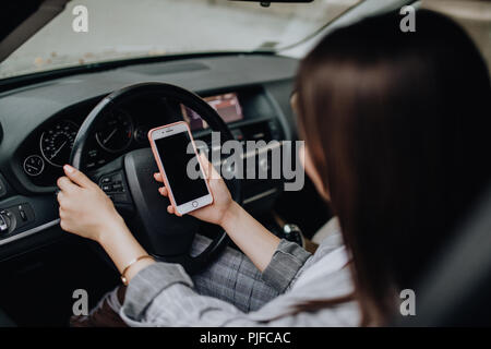 Business woman sitting in car and using her smartphone. Mockup image with female driver and phone screen - Stock Photo