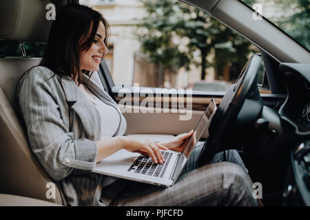 Businesswoman with a laptop in her car - Stock Photo