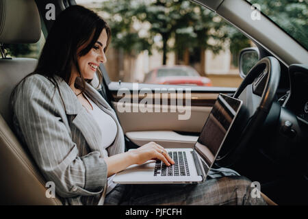 Beautiful young business woman using laptop and phone in the car. - Stock Photo