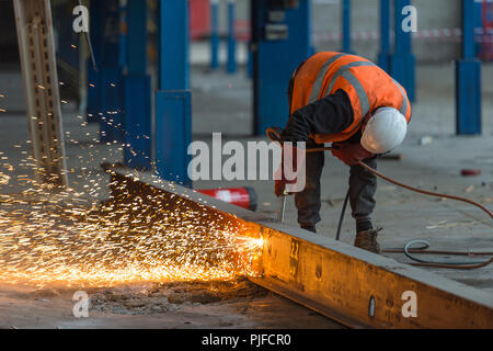 Building site worker cutting a beam with an acetylene torch - Stock Photo