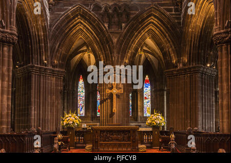Glasgow, Scotland, UK - June 17, 2012: The Cathedral. Closeup of altar in secluded chancel. Cross above. Thick pillars and small stained glass windows - Stock Photo