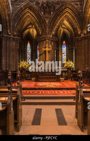 Glasgow, Scotland, UK - June 17, 2012: Closeup of altar in secluded chancel. Cross above. Thick pillars and small stained glass windows. Mostly browns - Stock Photo