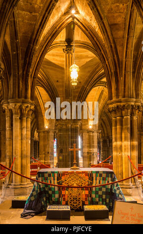 Glasgow, Scotland, UK - June 17, 2012: Closeup of altar in crypt of Glasgow Cathedral. Cross above. Thick pillars and ceiling. Mostly browns. - Stock Photo