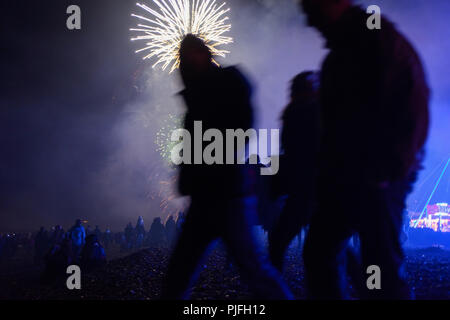 A hooded figure walks along the beach at night as fireworks explode in the sky behind him on bonfire night, fireworks night, November the 5th. - Stock Photo