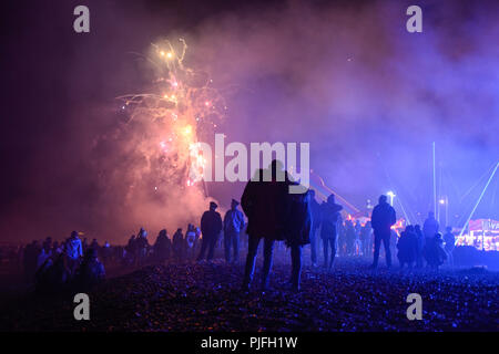 A couple hug on the beach as they watch fireworks explode above their heads in the night sky on Bonfire Night, Fireworks Night in Littlehampton - Stock Photo