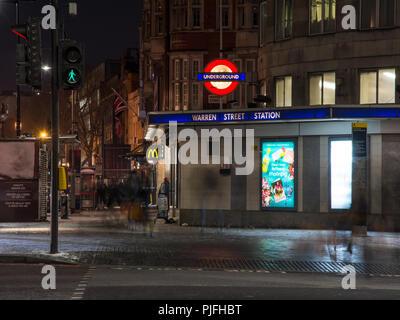 London, England, UK - February 27, 2018: Pedestrians walk along Tottenham Court Road outside Warren Street London Underground Station at night. - Stock Photo