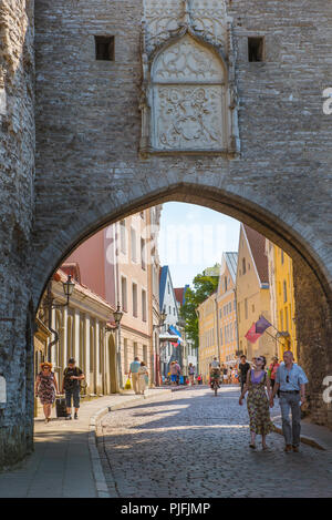 View of people walking under the arch of the Great Coast Gate on Pikk street at the north side of the medieval Old Town quarter in Tallinn, Estonia. - Stock Photo