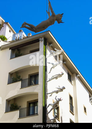 Italy, Tuscany, Florence, walking and flying scuptures on a building's facade - Stock Photo