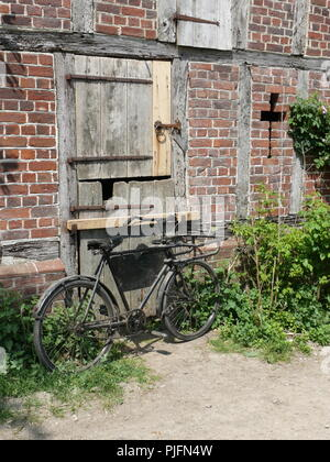 Old bicycle propped against an old wooden door, Suffolk, England - Stock Photo