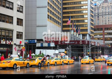 NEW YORK, USA - JULY 1, 2013: People walk along taxi filled 7th Avenue in New York.  As of 2012 there were 13,237 yellow taxi cabs registered in New Y - Stock Photo