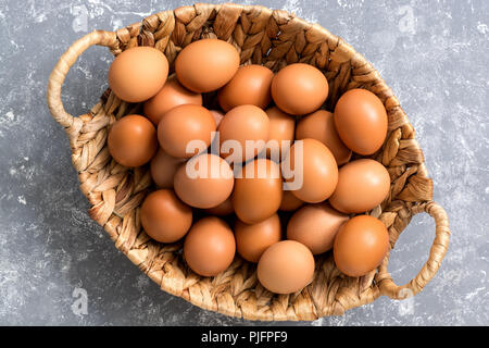 Close-up of a brown chicken egg in a basket on a gray background. Top view,flat lay - Stock Photo