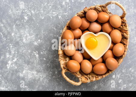 A raw egg in a bowl in the shape of a heart, a basket with brown eggs on a gray background. Top view, copy space, flat lay. - Stock Photo