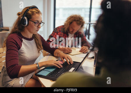 Computer programmers working at coworking space in tech startup office. Woman wearing headphones coding on laptop with colleagues working around the t - Stock Photo