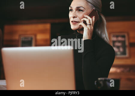 Portrait of beautiful senior woman sitting at coffee shop and talking on cell phone. Businesswoman making phone call while sitting at cafe. - Stock Photo