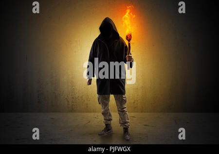 Ugly scary man with burning flambeau walking in an empty space - Stock Photo