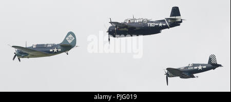 World War II US Navy aircraft flying in formation leader Curtiss SB2C-5 Helldiver, Grumman TBM-3E Avenger and Vought FG-1D Corsair in Thunder Over Mic - Stock Photo