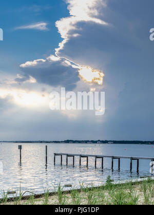 Light shining over pier on bay, the Hamptons, New York, USA. - Stock Photo